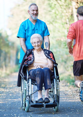 Pfleger ist mit Seniorin im Rollstuhl am Nachmittag unterwegs.