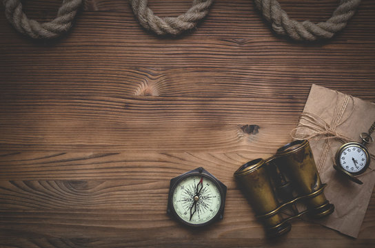 Travel or adventure flat lay background with a copy space. Binoculars, pocket watch, old parchment, mooring rope and a compass on a wooden table.