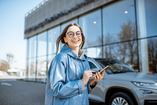 Lifestyle portrait of a young stylish woman in blue coat using smart phone near the modern car outdoors