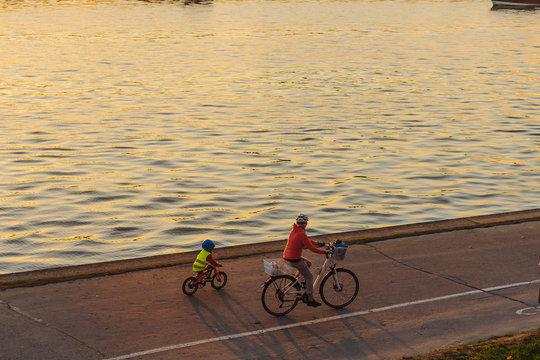 Mom and son ride bikes along the promenade