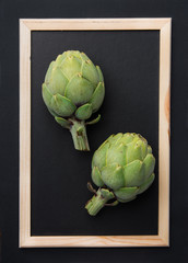Ripe green artichokes on chalkboard in picture frame black background. Creative food poster. Minimalist style. Mediterranean Spanish cuisine healthy plant based diet superfoods concept