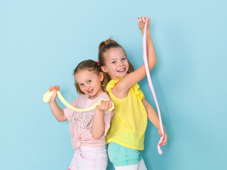 two beautiful girls playing with homemade slime and having a lot of fun in front of blue background