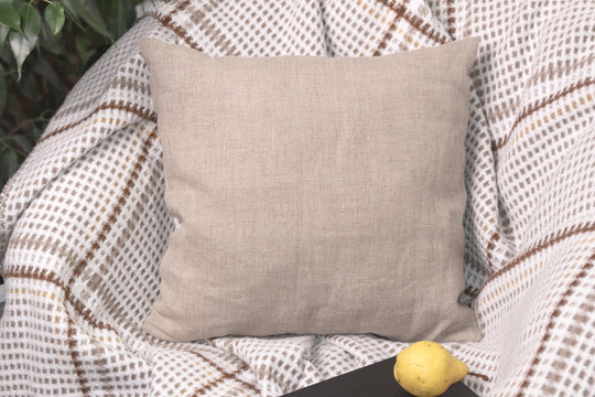 Natural linen pillow on a chair in cozy room, mockup