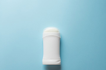 white deodorant on blue background. bath concept. place for text. copy space
