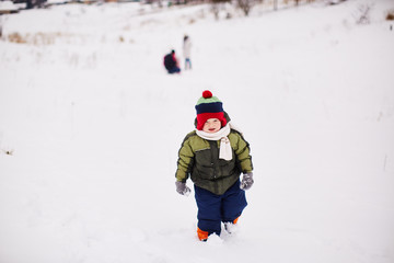 Little boy is running somewhere in the snow