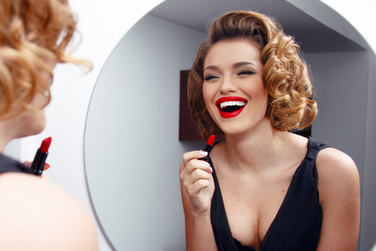 Elegant, smiling young woman, model with charming hairstyle and evening make up, applying red lipstick on sensual lips.