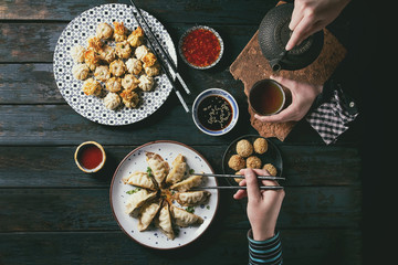 Overhead view of hands reaching for Dim sum Gyozas and pouring tea