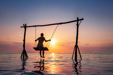 Happy girl relaxing at the beach on rope swing above sea water at sunset, summer vacation holidays...