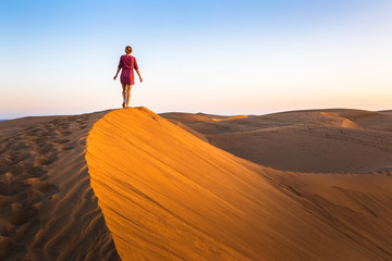Girl walking on sand dunes in arid desert at sunset and wearing dress, scenic landscape of Sahara or Middle East Wall mural