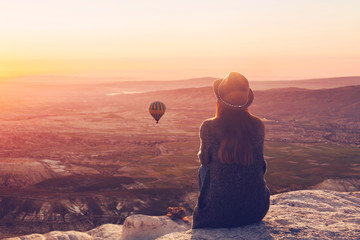 A woman on top of a hill alone admires the tranquil natural landscape and balloon and enjoys...