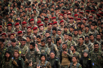 Kurdish fighters from the People's Protection Units (YPG) take part in a military parade as they celebrate victory over the Islamic state, in Qamishli