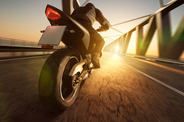 Fototapete - Motorrad fährt über Brücke im Sonnenuntergang