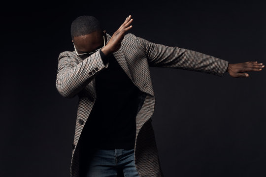 Serious cool man in black sweater and brown plaid coat and jeans. Studio, dark key