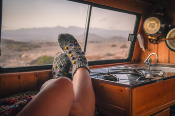 Woman feet in warm socks on vintage van. Mountain summer trip. Nomad life, girl legs in cute knitting sock near the window. Freedom travel concept. Autumn weekend. Female leg in an old wooden camper