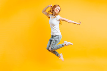 Portrait of a cheerful enthusiastic girl in a white T-shirt jumping for joy on a yellow background Wall mural