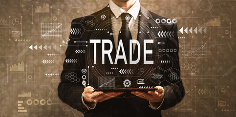 Trade with businessman holding a tablet computer on a dark vintage background