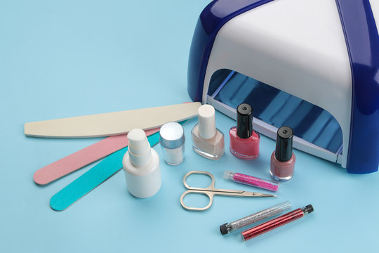Manicure. nail polishes, UV lamp and various accessories and tools for manicure on a trendy blue background.
