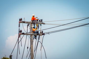Electrician working on power pole