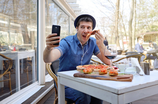Handsome hunger man eating pizza and showing off in a video conference with his friends. Traveler abroad and free roaming concept.