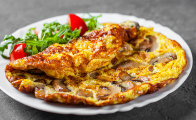 omelette with mushrooms and arugula salad in white plate on Dark grey black slate background