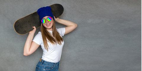 Teenager girl in sunglasses and hipster millennial hat with skateboard near the colorful wall,...