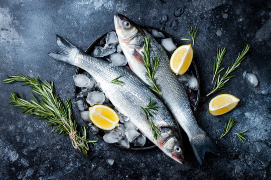 Fresh raw seabass fish on black stone background with spices, herbs, lemon. Culinary seafood background with ingredients for cooking. Top view