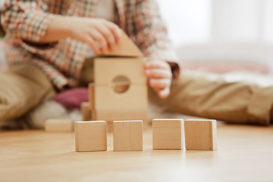 Little child sitting on the floor. Pretty boy palying with wooden cubes at home. Conceptual image with copy or negative space and mock-up for your text