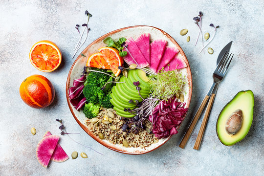 Vegan, detox Buddha bowl with quinoa, micro greens, avocado, blood orange, broccoli, watermelon radish, alfalfa seed sprouts. Top view, flat lay