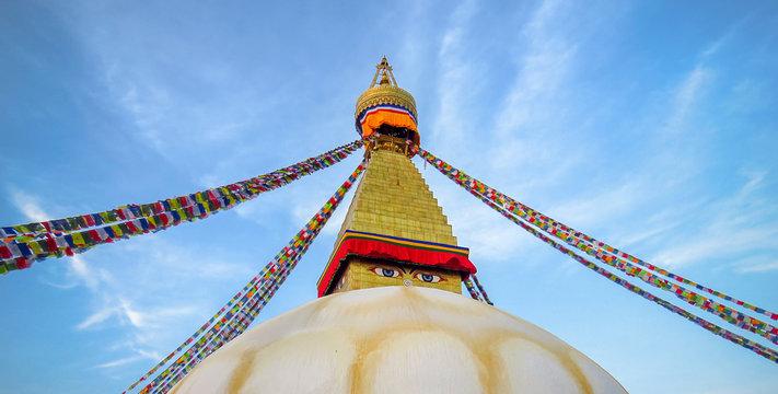 Top of Boudhanath stupa, eyes watching, prayer flags, blue sky, Kathmandu, Nepal