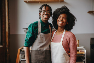 Portrait of happy female chef with male student standing against wall in workshop