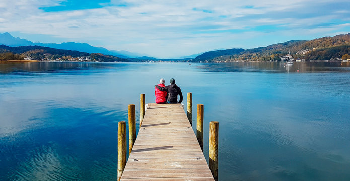 Couple sitting and hugging at the pier by Wörtersee, Pörtschach, Austria. Beautiful lake landscape, surrounded by Alps. This lake is natural drinking water tank. Love is in the air. Romantic moments.