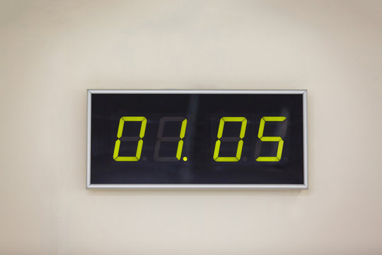 Black digital clock on a white background showing time 01.05