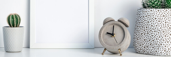 Shelf at home against a white wall. A mockup frame with space for text or graphics. Cactus decoration in pots. Scandinavian style. Concrete clock. Panoramic real photo