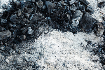 Ash and charcoal cooled after burning. Extinguished and cooled down fire made of wood. Background of coals and ash texture.