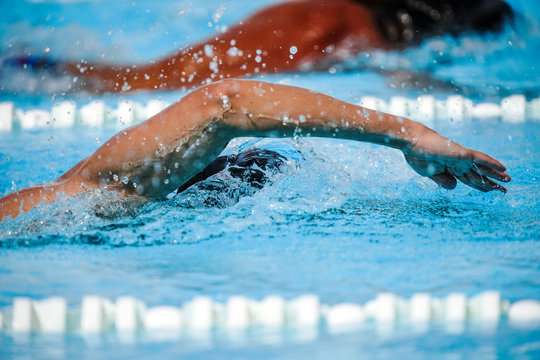 Details with a professional athlete swimming in an olympic swimming pool