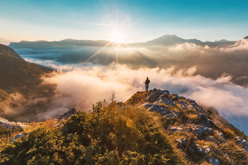 Successful hiker enjoying at top of mountain above clouds Wall mural