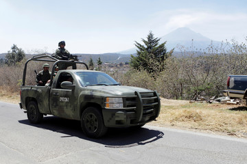 Soldiers check an evacuation route after Mexican authorities raised the alert level for the Popocatepetl volcano (in the background) following an increase in its activity, in San Nicolas de los Ranchos