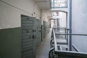 Old prison corridor with open cells.