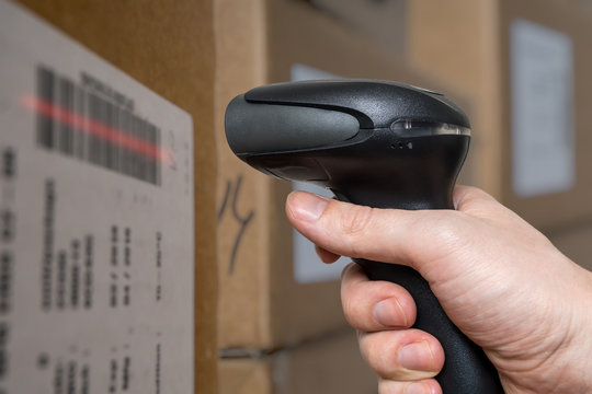 Scanning barcode with bar code reader on packages in warehouse.