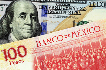 A close up image of a new American one hundred dollar bill with a Mexican one hundred peso bank note in macro