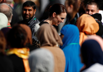 New Zealand's Prime Minister Jacinda Ardern speaks with relatives of victims of the mosque attacks at the national remembrance service at Hagley Park
