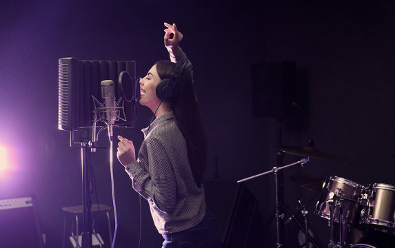 Young singer with microphone recording song in studio. Space for text
