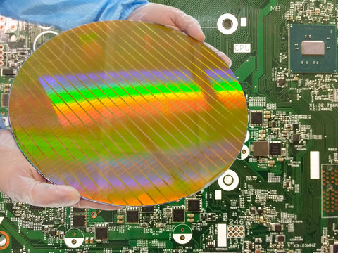 holding a Silicon wafers inspection,detail of a silicon wafers reflection light or Reflection,  on pcb background,