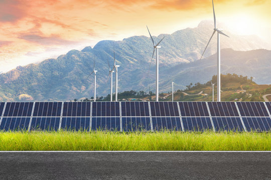 Asphalt road with solar panels with wind turbines against mountanis landscape against sunset sky,Alternative energy concept