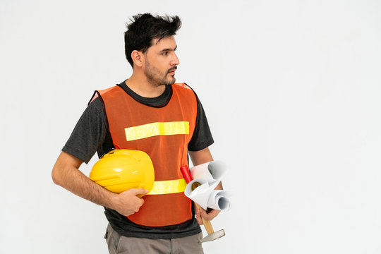Young male handsome construction worker standing on white background. Civil engineering concept.