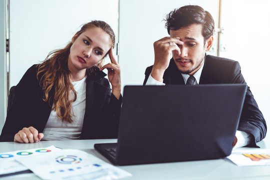 Unhappy serious businessman and businesswoman working using laptop computer on the office desk. Bad business crisis situation and bankruptcy concept.