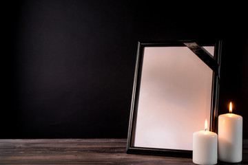 Blank funeral frame and candles on table against black background