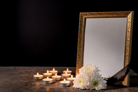 Blank funeral frame, candles and flowers on table against black background