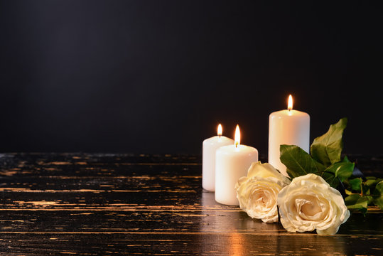 Burning candles and flowers on table against black background