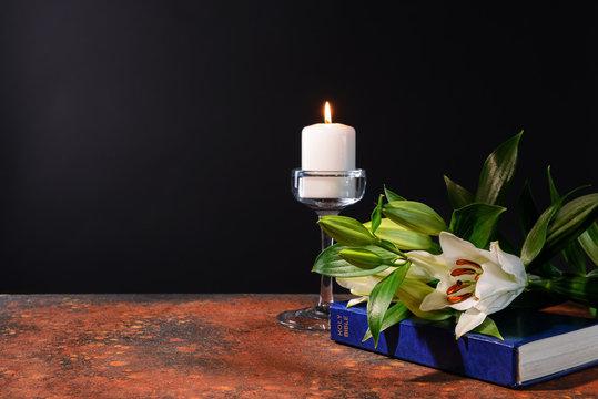 Burning candle, Bible and flowers on table against black background